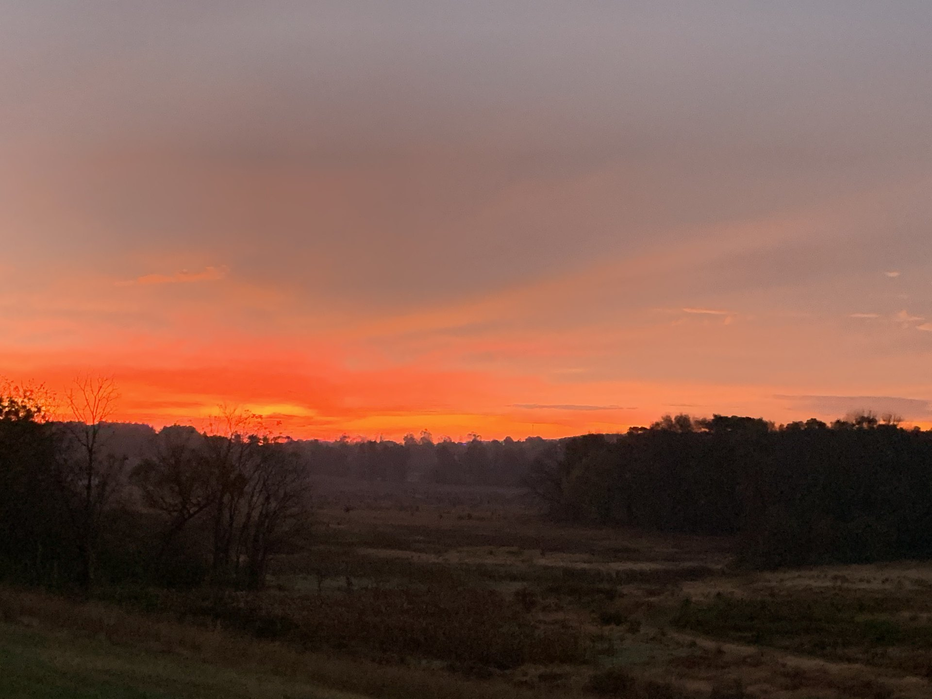 Revelation 9 NASB.  A fiery red sky at sunrise over a large, open field.