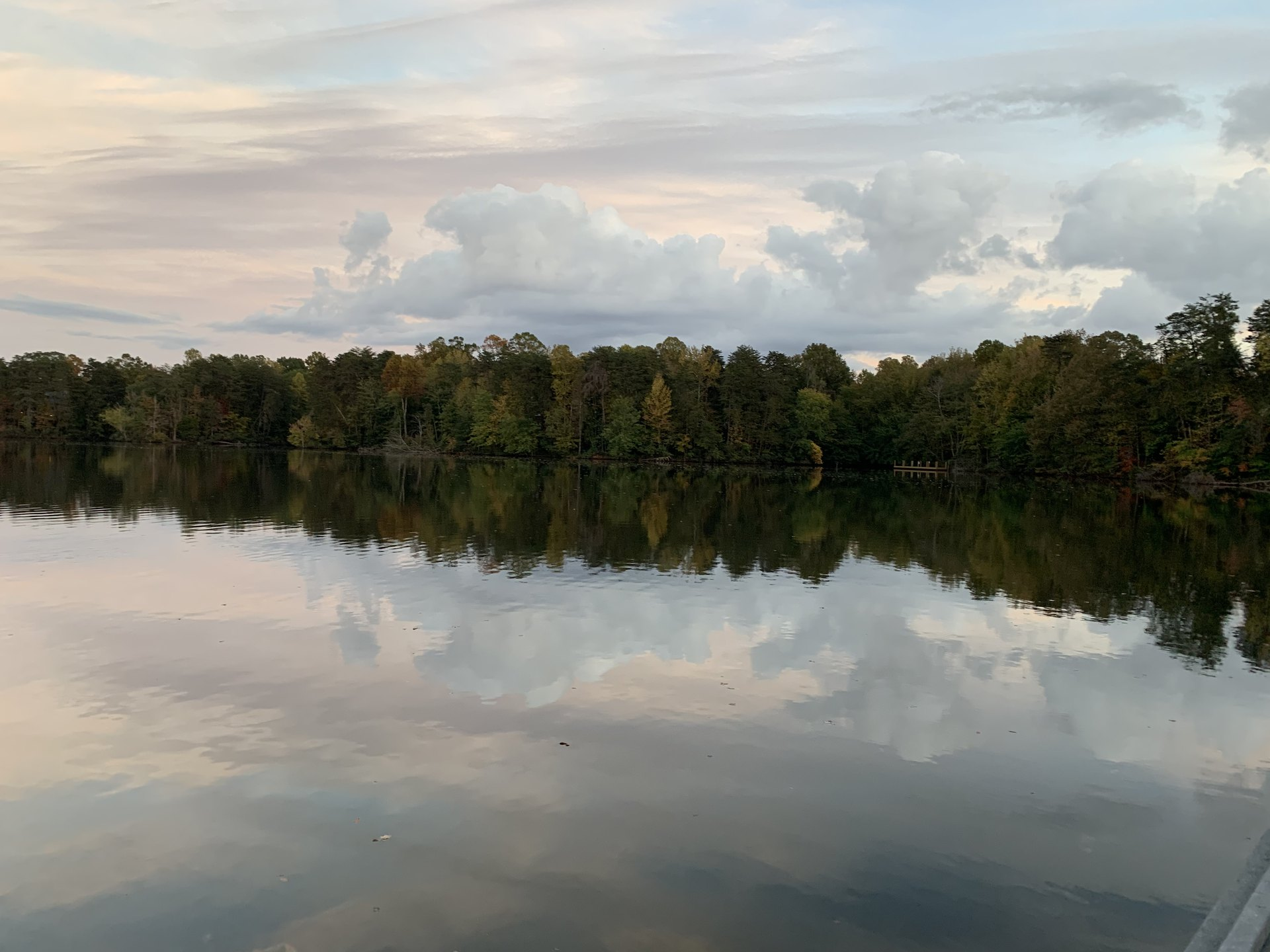 James 4 NASB.  Autumn trees and grey skies with white, fluffy clouds reflecting on a lake.