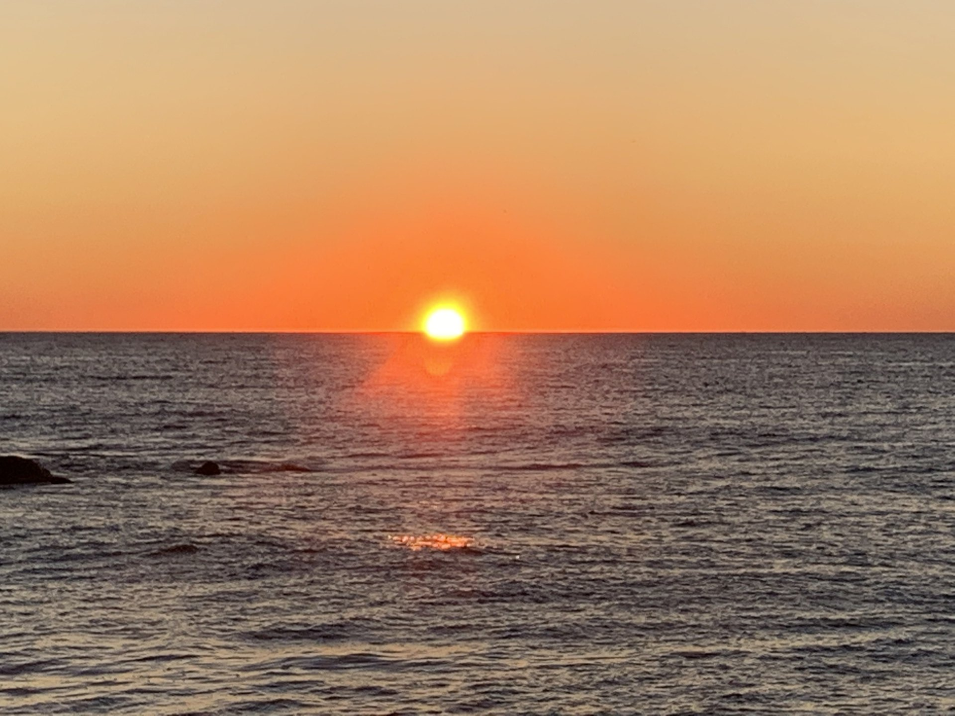 2 Peter 1 NASB.  The bright, red sun rising above the ocean horizon.